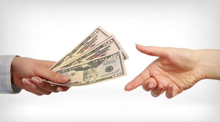A hand giving money to another hand